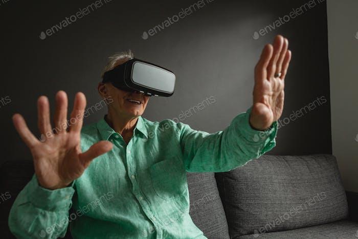 Vorderansicht der aktiven älteren kaukasischen Mann mit Virtual Reality Headset im Wohnzimmer zu Hause