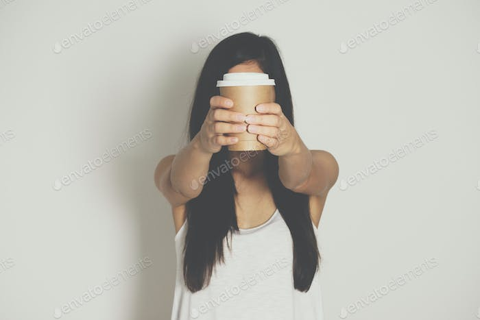 Woman holding brown paper cup of hot coffee.