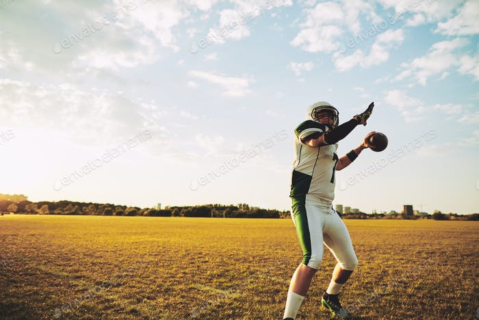 Football quarterback throwing a long pass during team practice