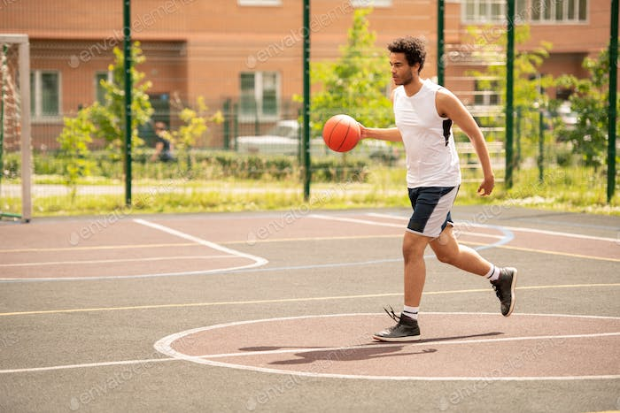 Young basketballer in sportswear with ball running down playground