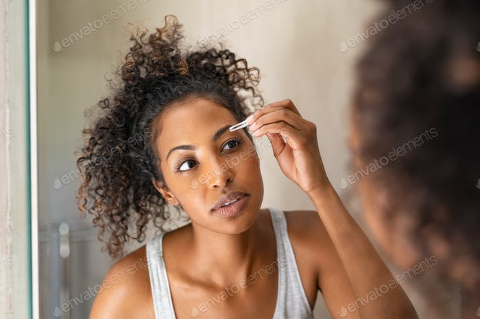 African woman plucking eyebrows