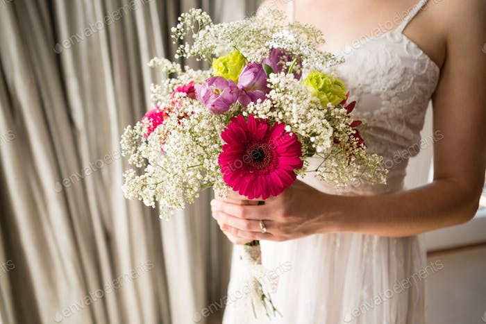 Midsection of bride in wedding dress holding bouquet at home