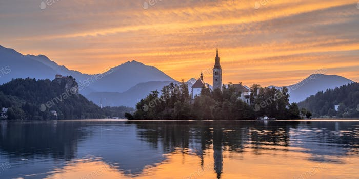 Lake bled with church under orange sky