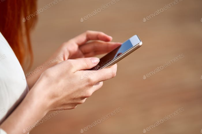 Faceless young woman is holding smartphone and typing