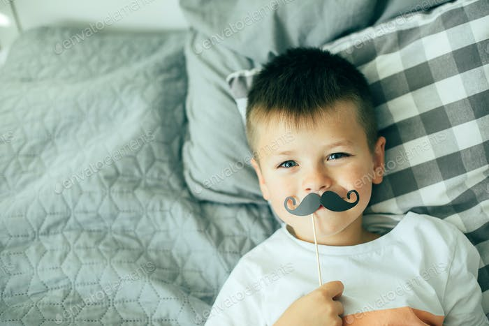 Portrait of funny kid with fake mustache. Happy child playing in home. Lifestyle concept