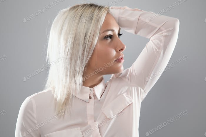Beautiful female model in shirt holding her blonde hair