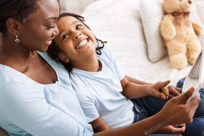 Black family using digital tablet at home