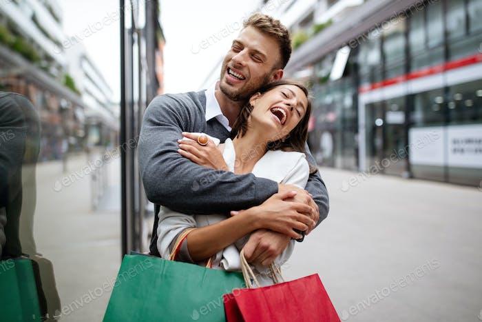 Beautiful young couple enjoying in shopping, having fun together