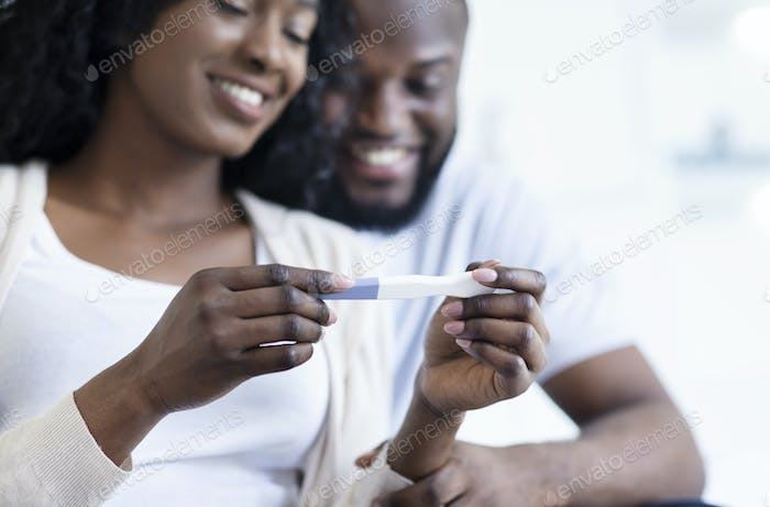 Black maried couple holding pregnancy test, happy with positive result