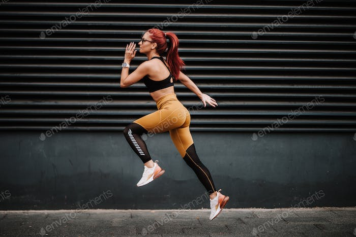 Sports and fitness concept - Sexy woman with fit body jumping and running, exercising