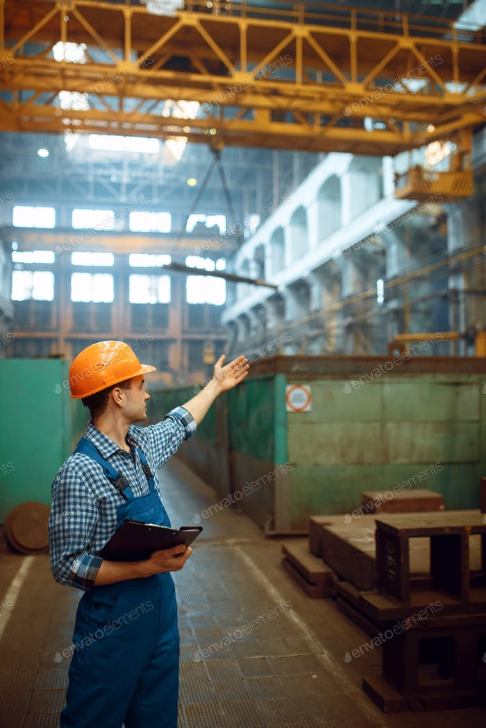Master looks at work of crane operator on factory