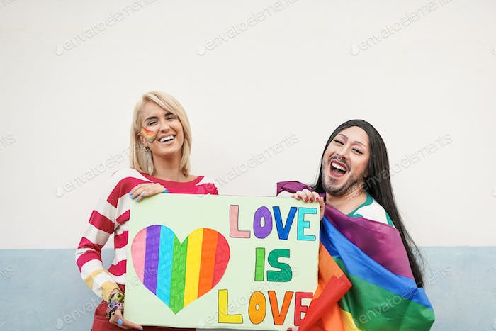 Happy gay people with love is love banner at gay pride parade - Homosexual and transgender women