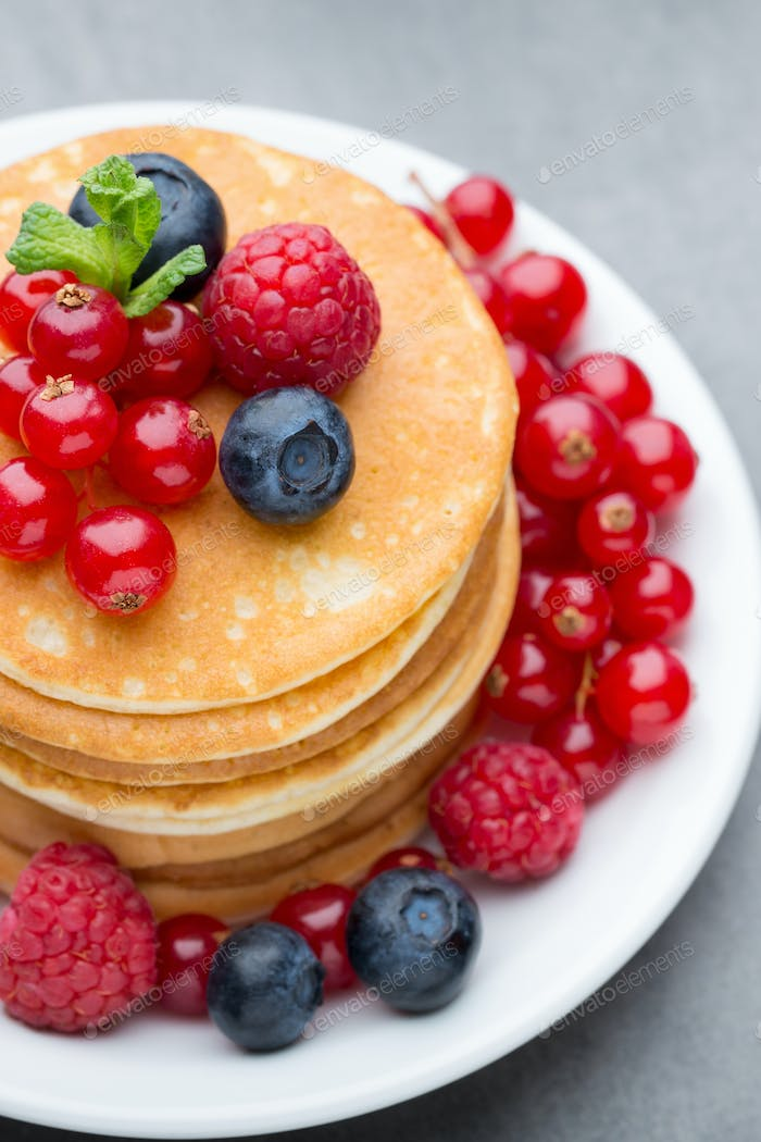 Stack of pancakes with blueberry and fresh berry.