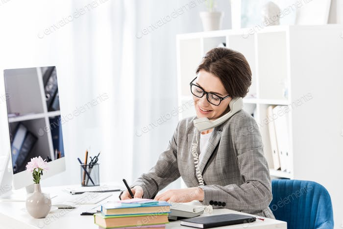 smiling attractive businesswoman talking by stationary telephone in office