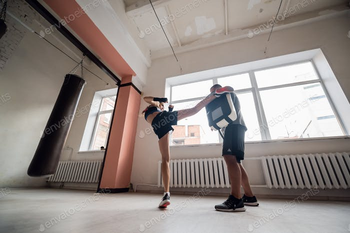 Eine junge Sportlerin in guter körperlicher Verfassung führt Kickboxtraining unter der Aufsicht von