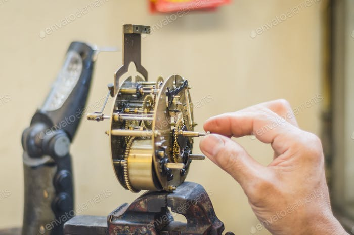 man fixing an old clock mechanism
