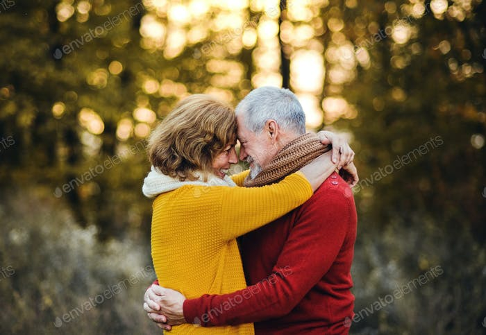 A senior couple standing in an autumn nature at sunset, hugging.