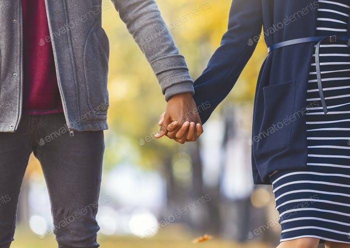 African american couple in love holding hands while walking