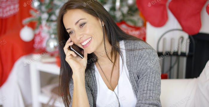 Young woman making Christmas calls to friends