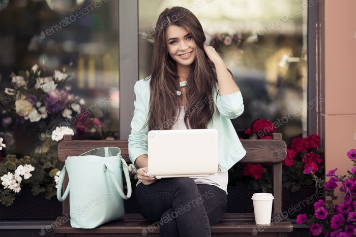 Smiling Young Woman Sitting On The Bench And Using Laptop