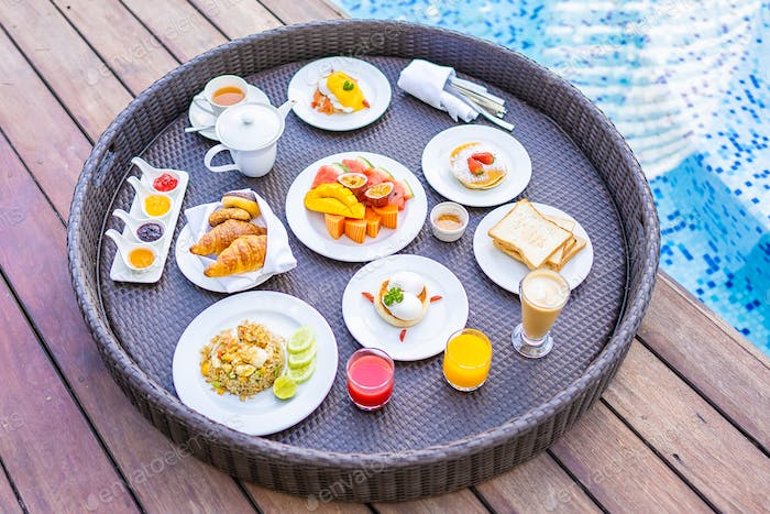 Flotaing breakfast tray around outdoor swimming pool with bread fruit egg coffee and juice