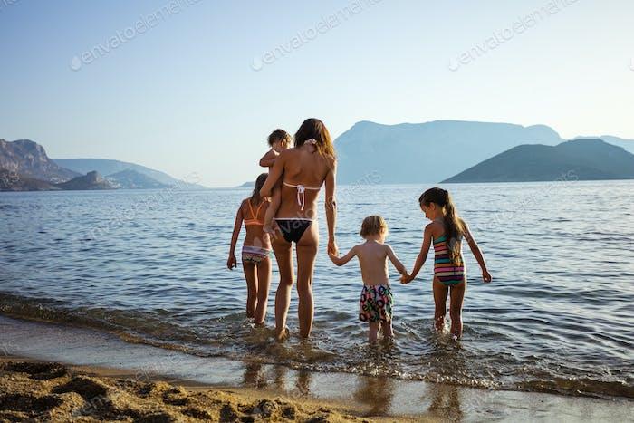 Junge Frau mit vier Kindern zu Fuß in seichten Meerwasser