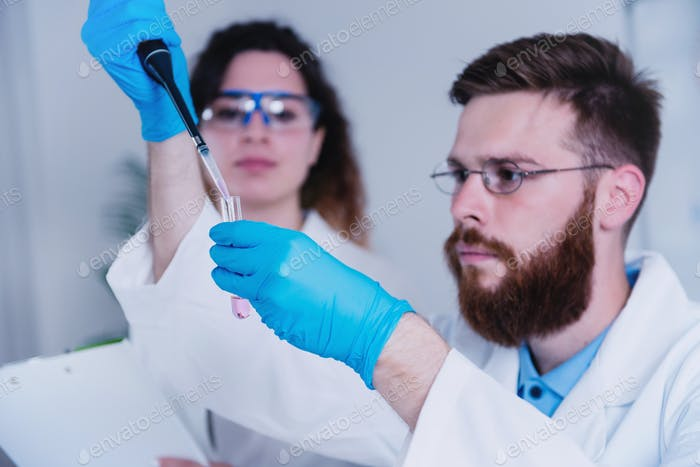 Young Male Researcher Holding Dropper And Test Tube