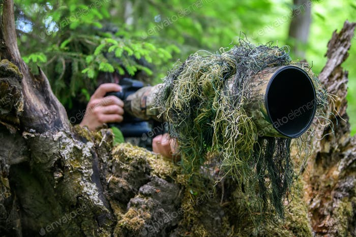Wildlife photographer in the summer ghillie camouflage suit