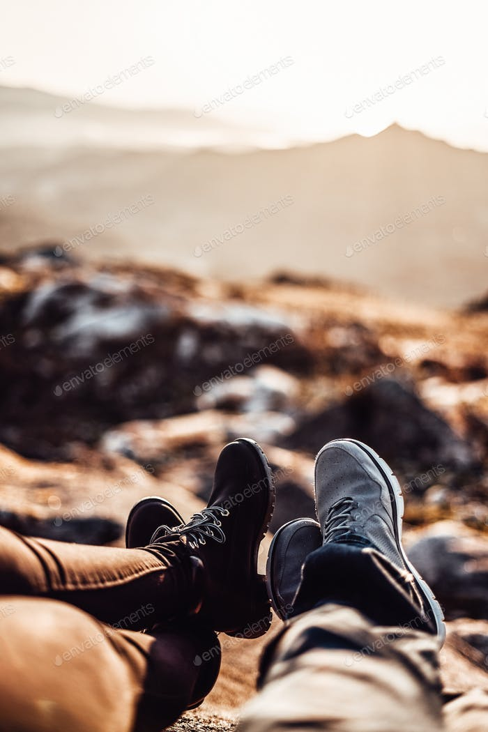 Detail of two pair of feet in front of a defocused landscape at sunset
