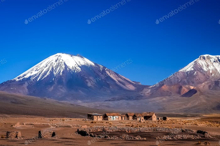 Abandoned village at the foot of two enormous volcanos