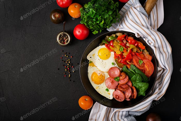 Fried eggs with sausage and vegetables in a frying pan