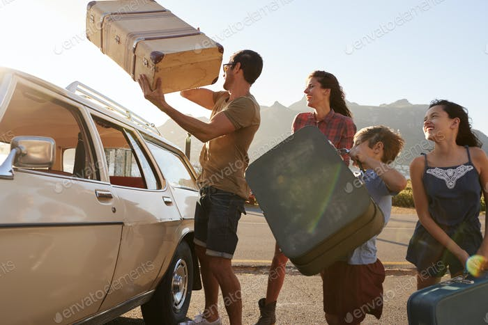 Family Loading Luggage Onto Car Roof Rack Ready For Road Trip