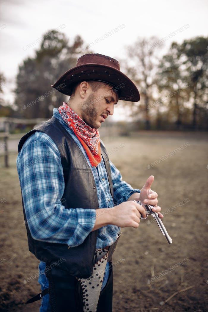 Cowboy checks revolver before gunfight on ranch