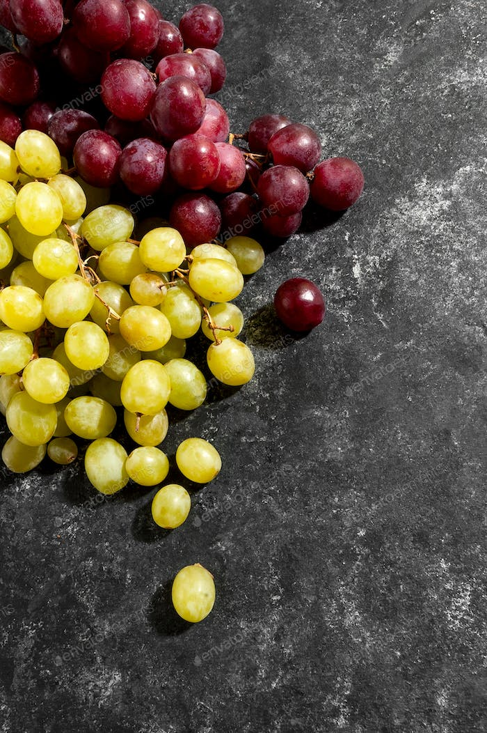 White and red grapes on a black aged background.