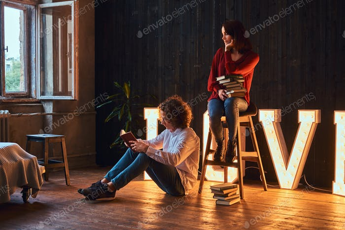 Student couple with books in a room decorated with voluminous letters with illumination.