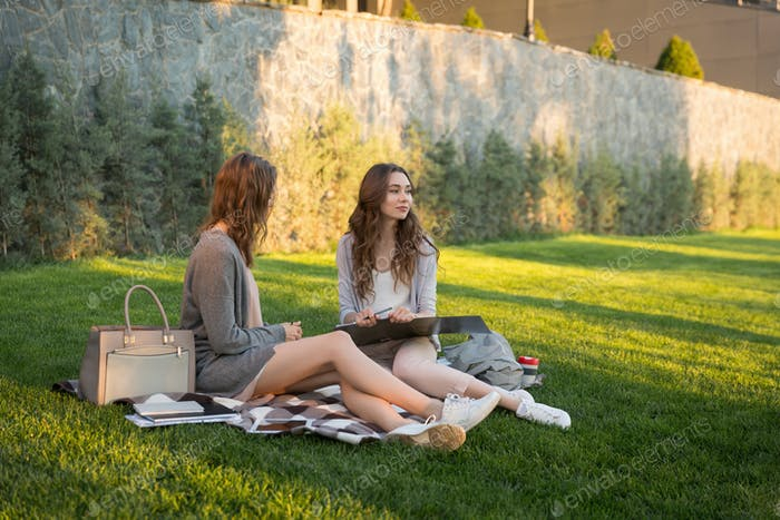 Happy young two women sitting outdoors in park writing notes