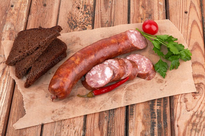 Boiled and smoked sausage on a wooden surface.