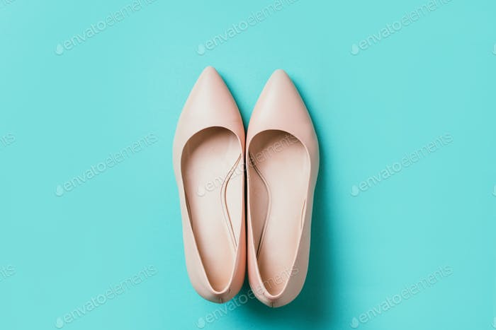 Nude beige color high heel shoe on blue background. Top view. Copy space. Flat lay. Woman mock up