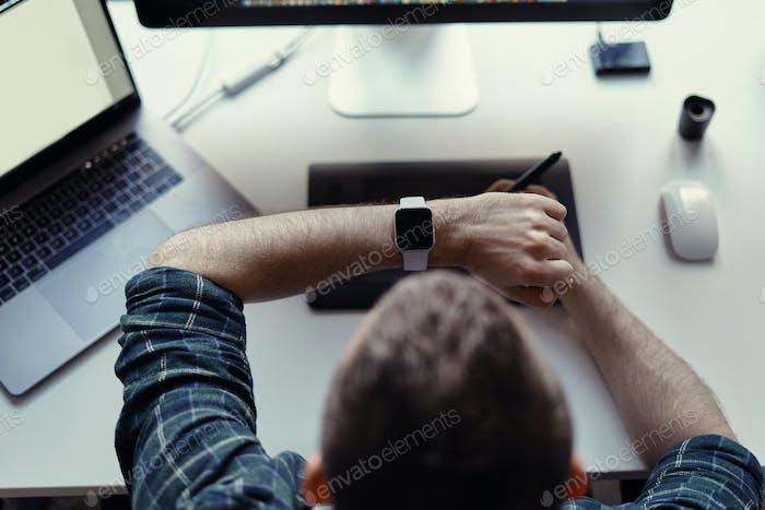 Hombre viendo reloj inteligente mientras trabaja
