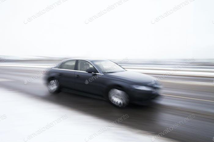 Blurred motion of car on street during winter