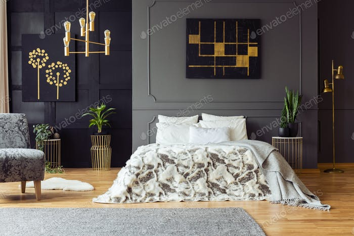 Black and gold poster on grey wall above bed in bedroom interior