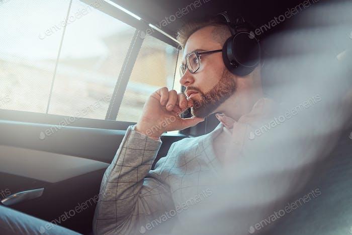 exitoso hombre de negocios con estilo en un traje gris en un asiento trasero en un coche de lujo.