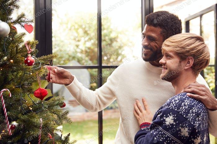 Gay Male Paar zu Hause Hängende Dekorationen auf Weihnachtsbaum zusammen
