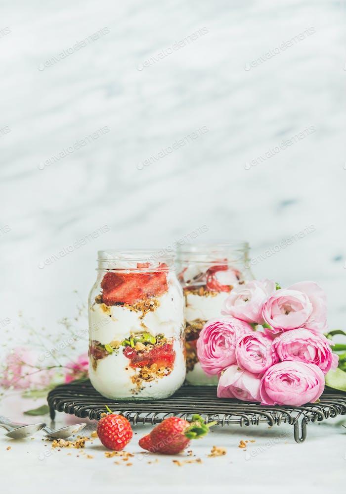 Greek yogurt, granola, fresh strawberry breakfast in jars, raninkulus flowers