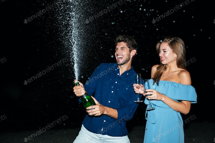 Couple opening bottle of champagne and having fun at night