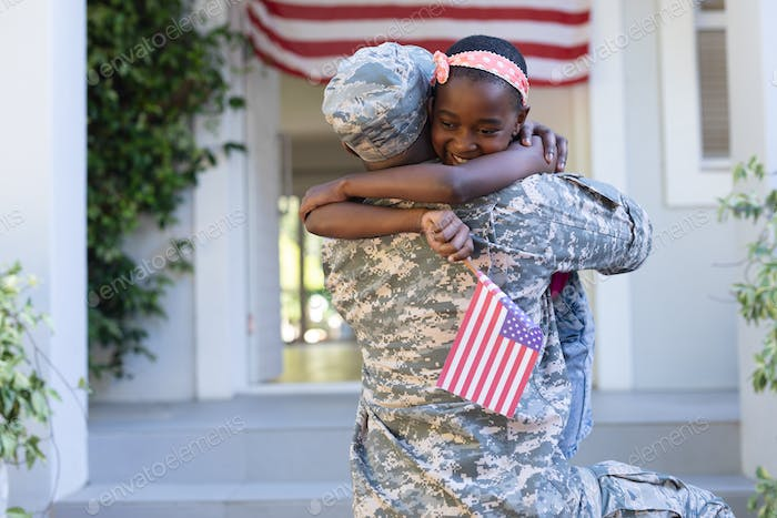 African american soldier father hugging smiling daughter holding flag in front of house