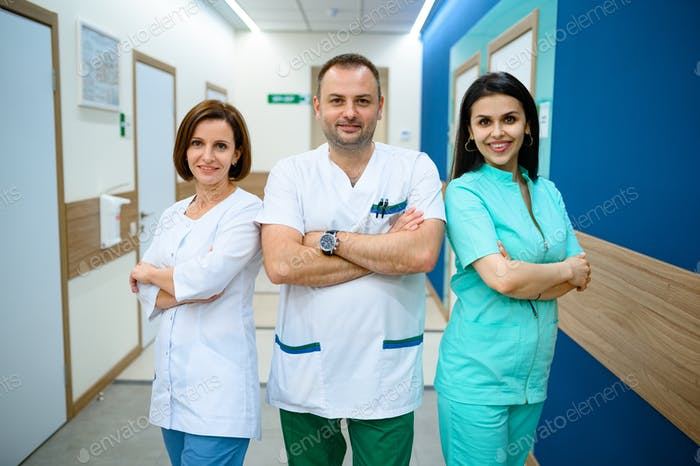 Three smiling doctors standing in clinic corridor