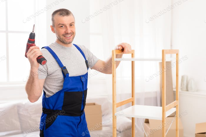 Furniture Assembler Posing With Electric Drill Assembling Cabinet Indoor