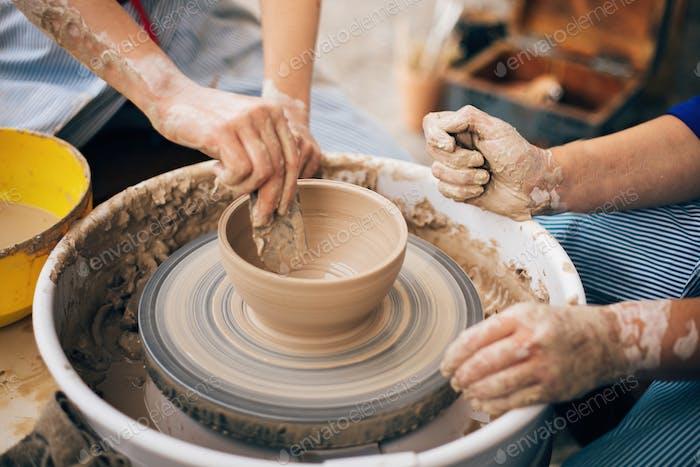 Руки взрослых и детей делают керамику, работают с влажной глиной крупным планом