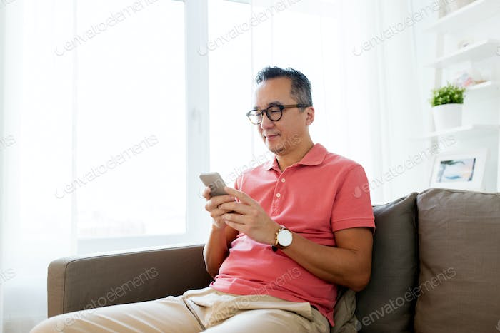 asian man with smartphone sitting on sofa at home